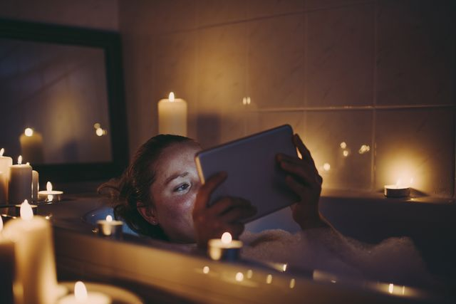 woman using tablet pc in bathtub