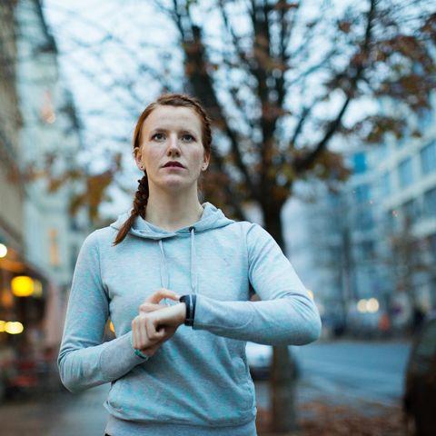 Woman using watch before exercising on sidewalk