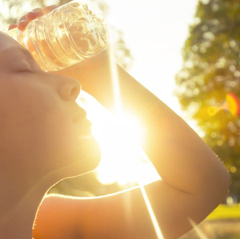 Woman using water bottle to cool down.