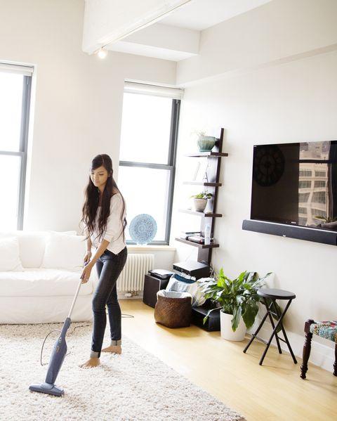 Woman vacuuming living room at home