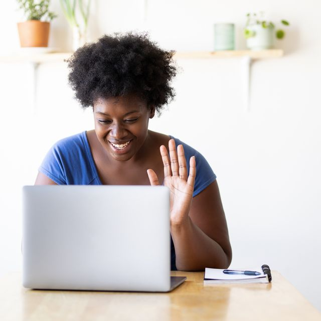 woman video calling using a laptop at home