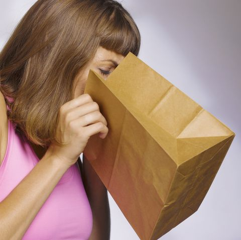 woman vomiting into paperbag