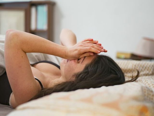 woman waking up and wiping her eyes