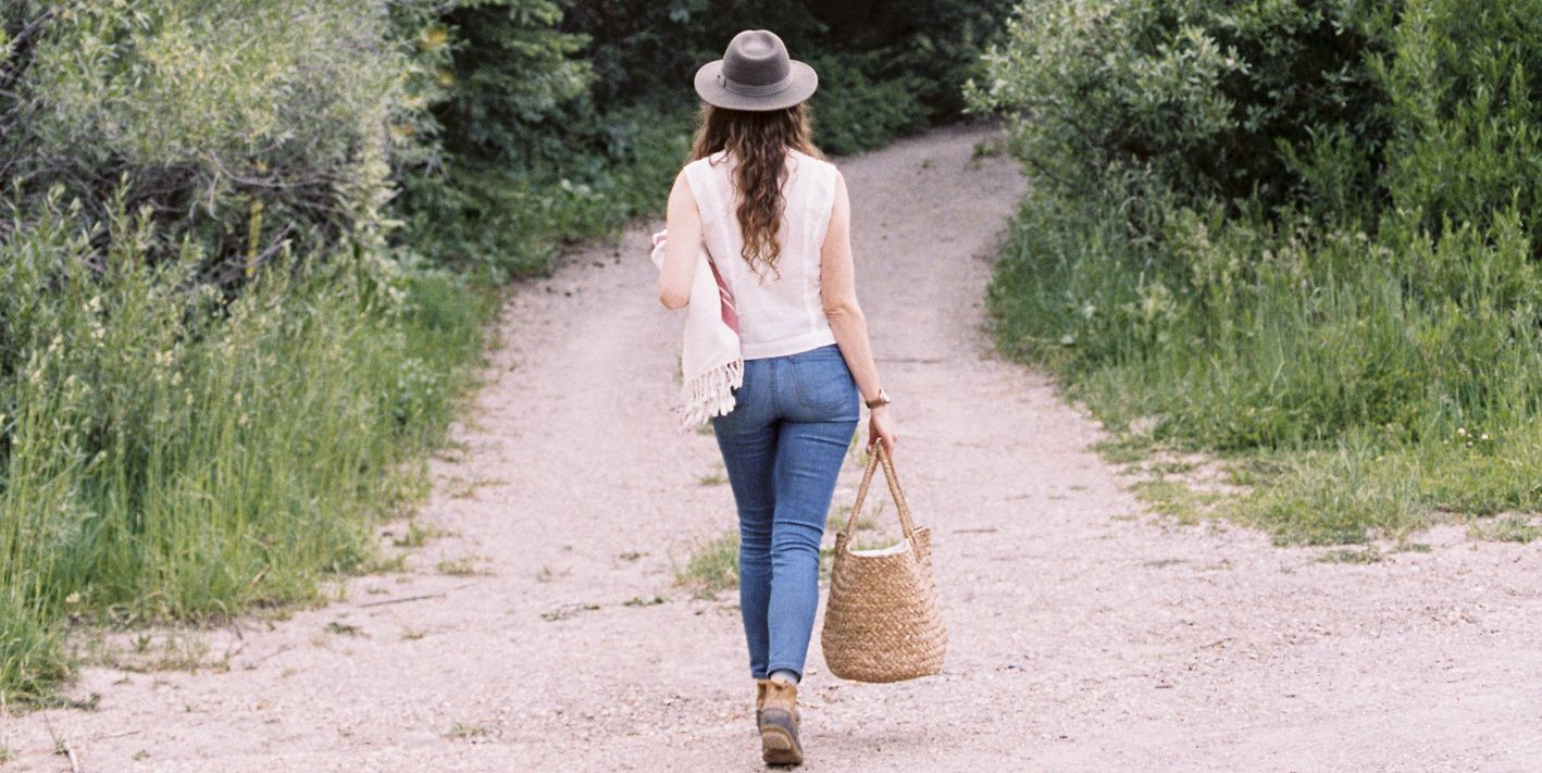 Woman walking along a forest path, carrying a bag.