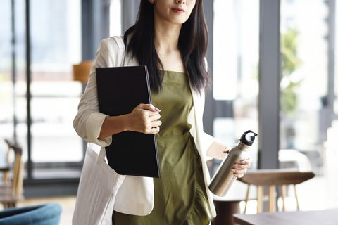 woman walking out of an office with laptop