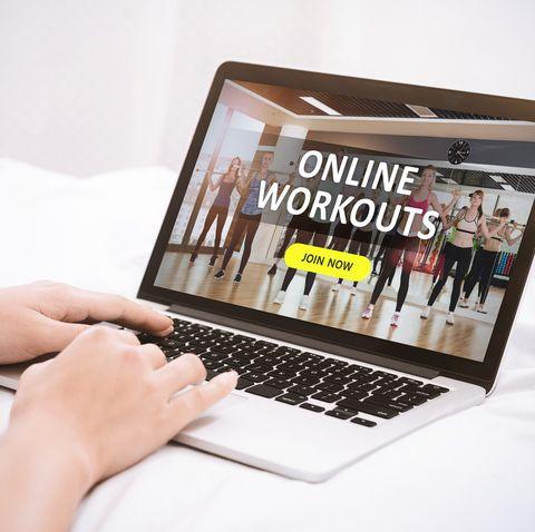 woman watching sport training online on laptop