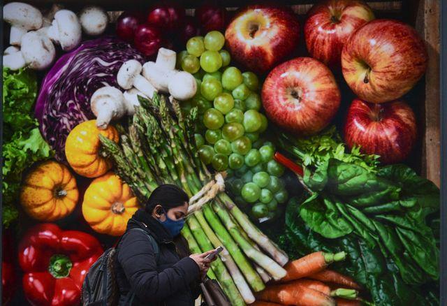 una mujer pasea delante de un cartel con frutas y verduras