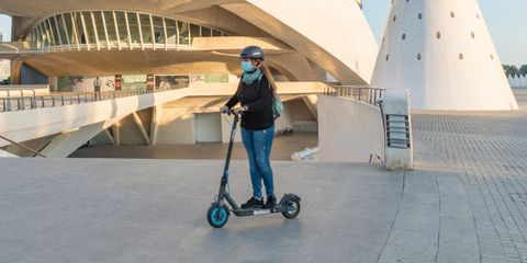 a woman wearing a face mask with a skateboard passes in