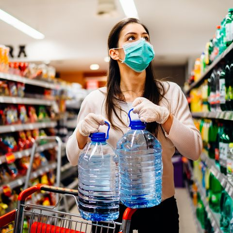 woman wearing face mask buying bottled water in supermarketdrugstore with sold out suppliesprepper buying bulk supplies due to covid 19 or coronavirus and panic buying concept