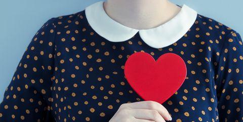 Woman wearing polka dot dress holding heart shape object
