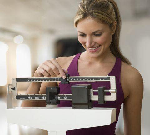 una mujer joven averigua cuánto pesa con una báscula de toda la vida
