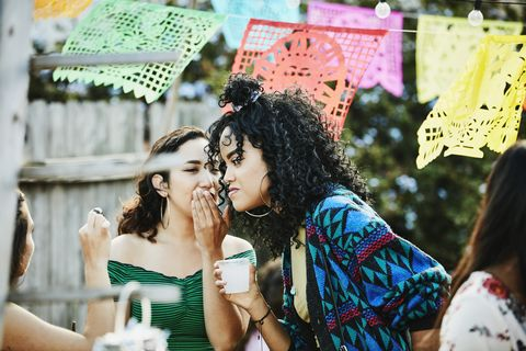 woman whispering to friend during backyard party on summer afternoon