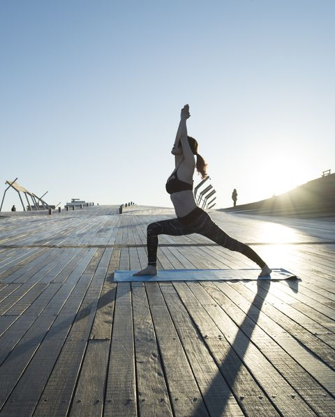 A woman who plays yoga outdoors.