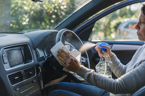 woman wiping down car steering wheel