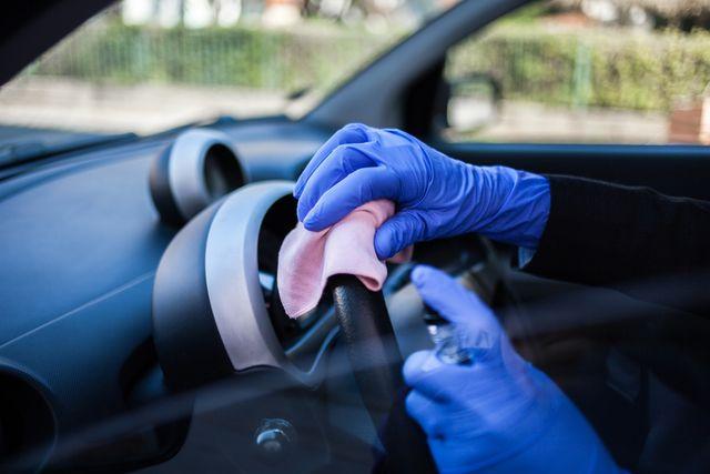 woman wiping down steering wheel