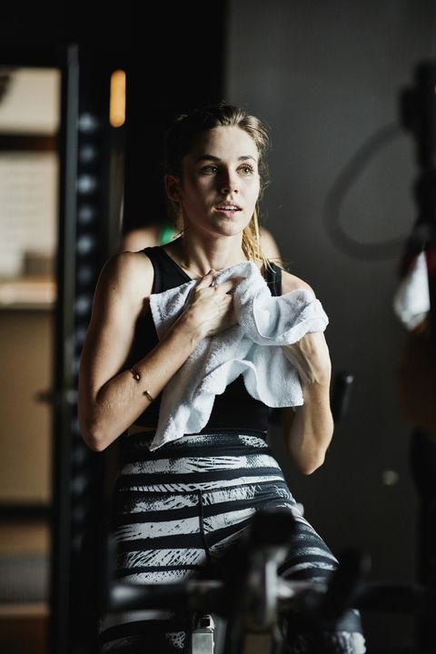 Woman wiping off sweat after indoor cycling class in fitness studio