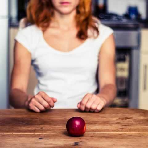 Woman with a nectarine in kitchen