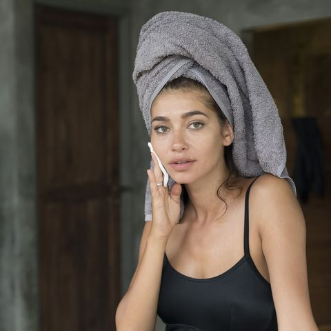 woman with a towel on hear head removing make up