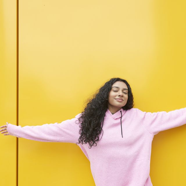 Woman with arms outstretched against yellow background