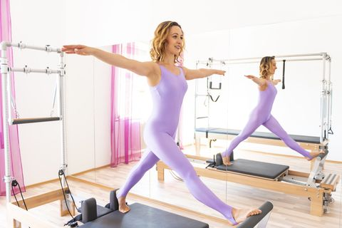 Woman With Bodysuit Exercising on Pilates Machine