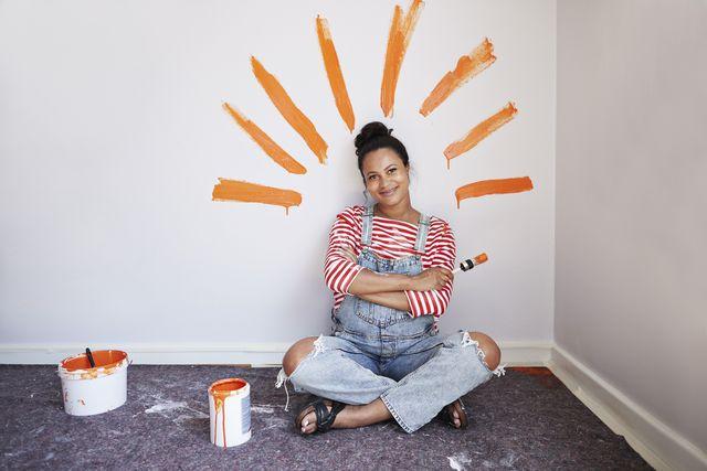 una ragazza seduta davanti a una parete da imbiancare