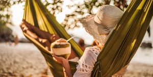 Woman with coconut drink relaxing in hammock at the beach.