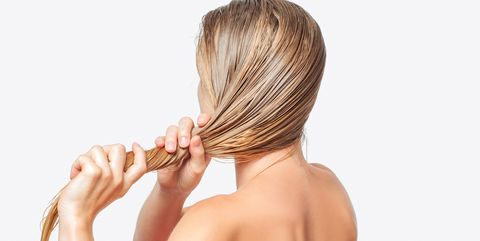 Woman with comb brushing her wet blonde hair on white background
