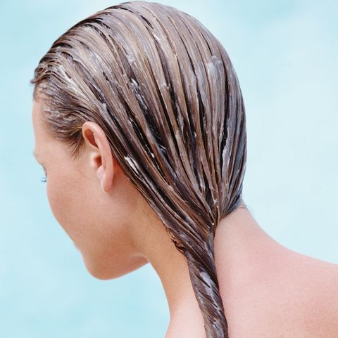 Woman with conditioner in hair, rear view