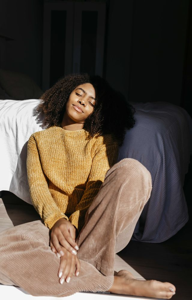 woman with eyes closed resting while sitting by bed at home
