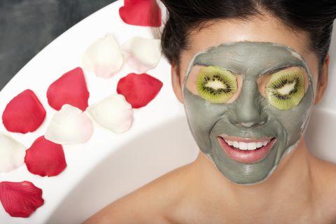 una mujer con una mascarilla facial y kiwi en la cara en una bañera