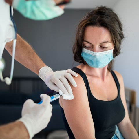 woman with face mask getting vaccinated  coronavirus concept