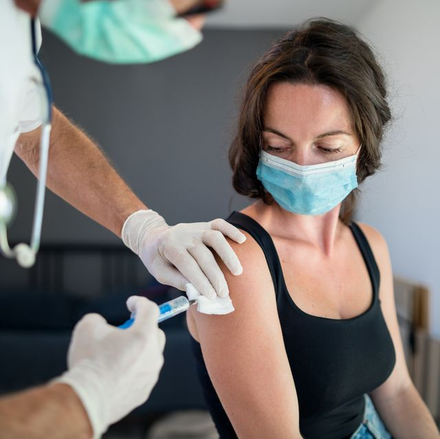 woman with face mask getting vaccinated, coronavirus concept