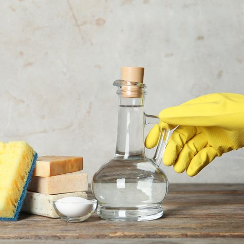 Woman with jug of vinegar and cleaning supplies at table