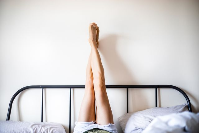 woman with legs raised wearing white shorts lying on bed