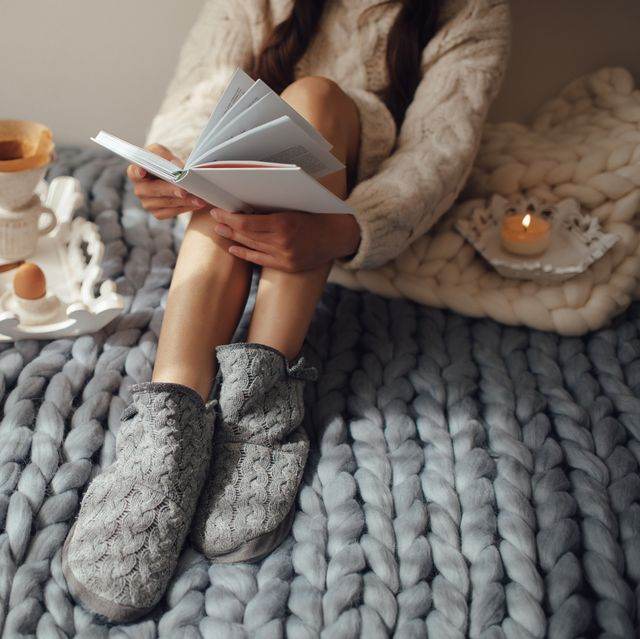 woman with long hair drinking hot coffee and reading book in bed woman in woolen socks and sweater sitting on wool chunky merino plaid cozy winter morning concept