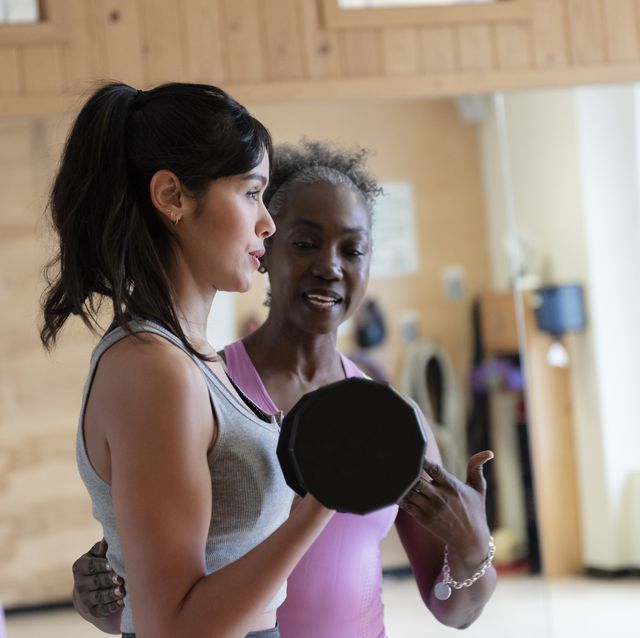 woman with personal trainer lifting weights in gym