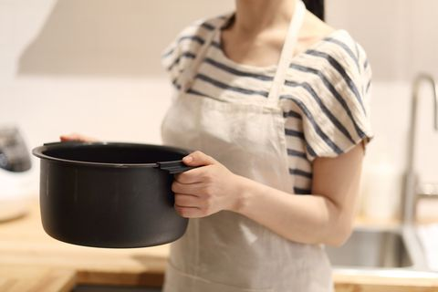 Woman with rice cooker in kitchen