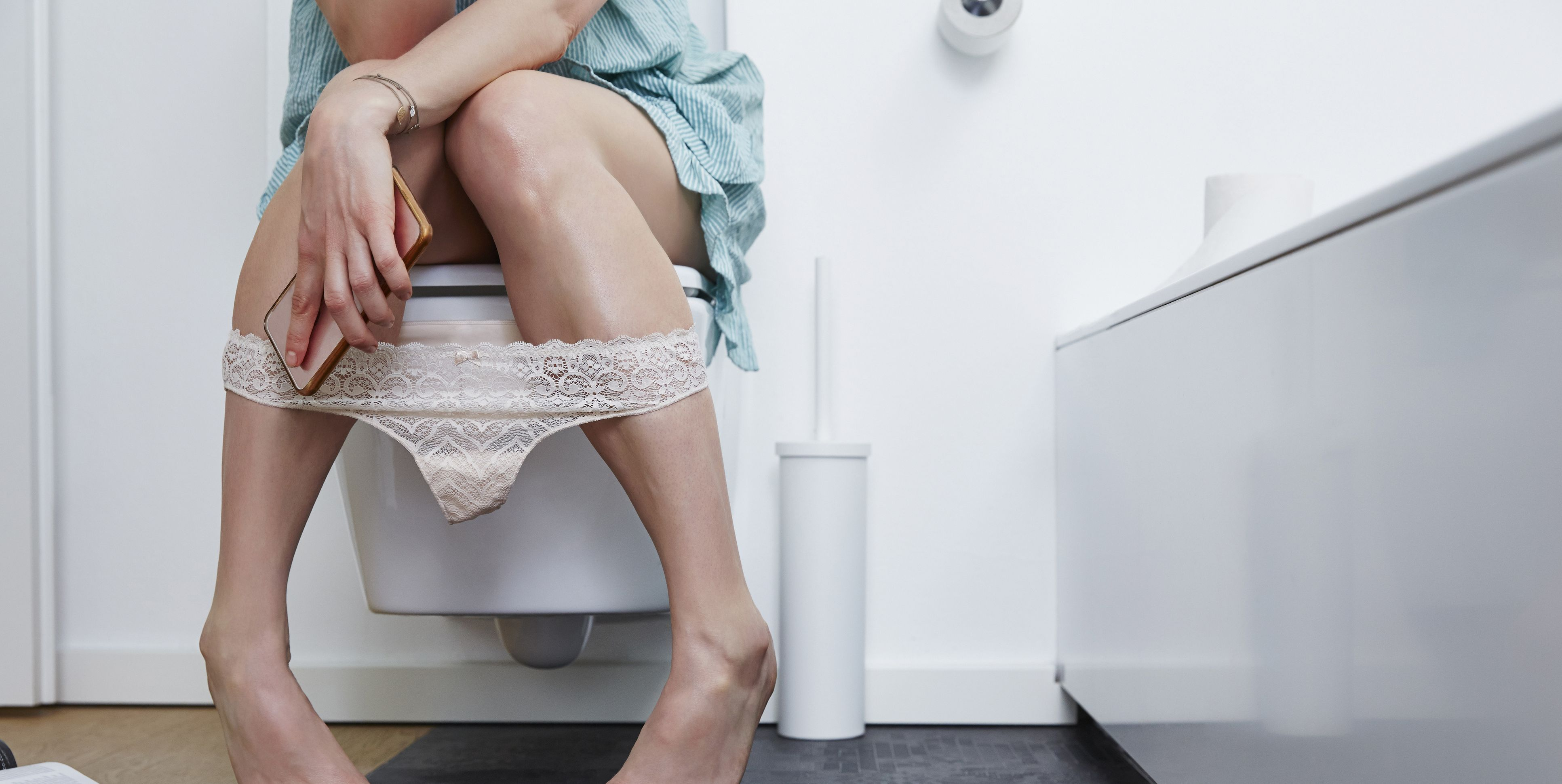Woman with smartphone on toilet