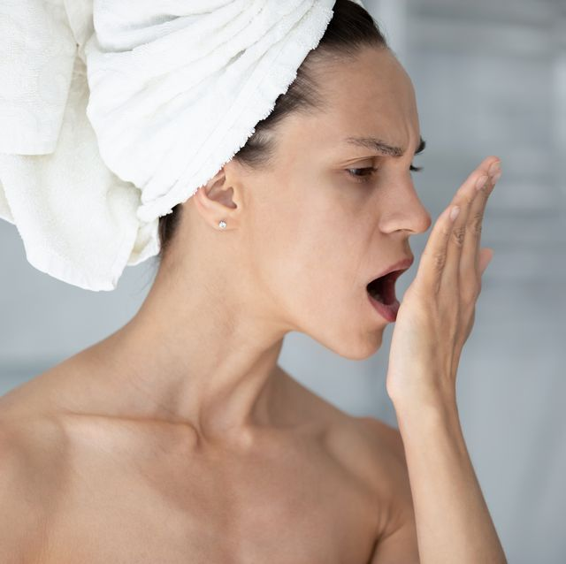 woman with towel on head opens mouth check breath