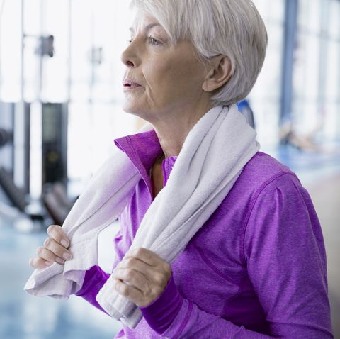 Woman with towel resting at gym