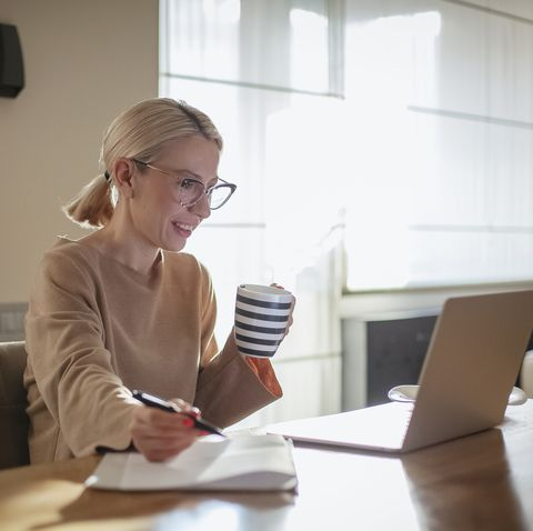 woman working at home while having breakfast