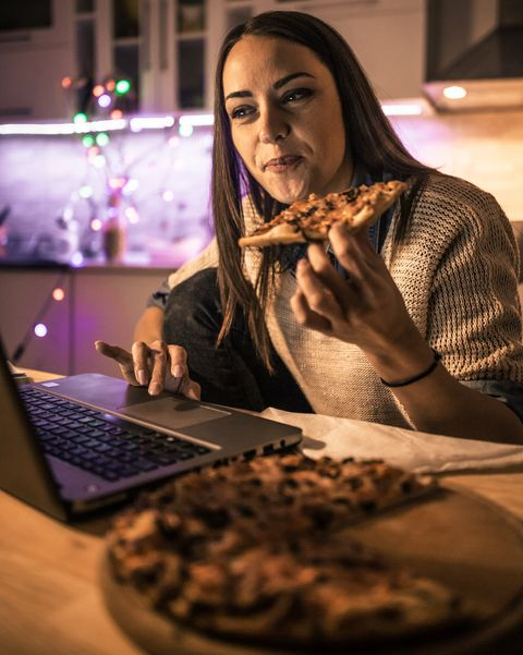 woman works at the computer and eating fast food