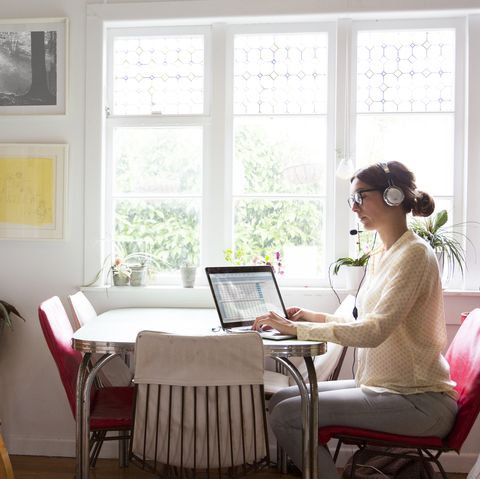 a woman works from her home at the table in her kitchen