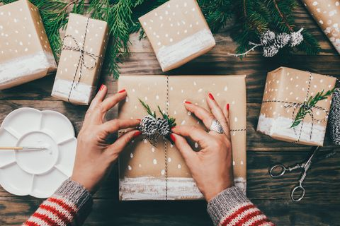 Woman wrapping Christmas presents in a crafty way