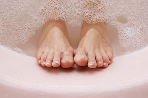 woman's feet resting against bath tub with bubbles