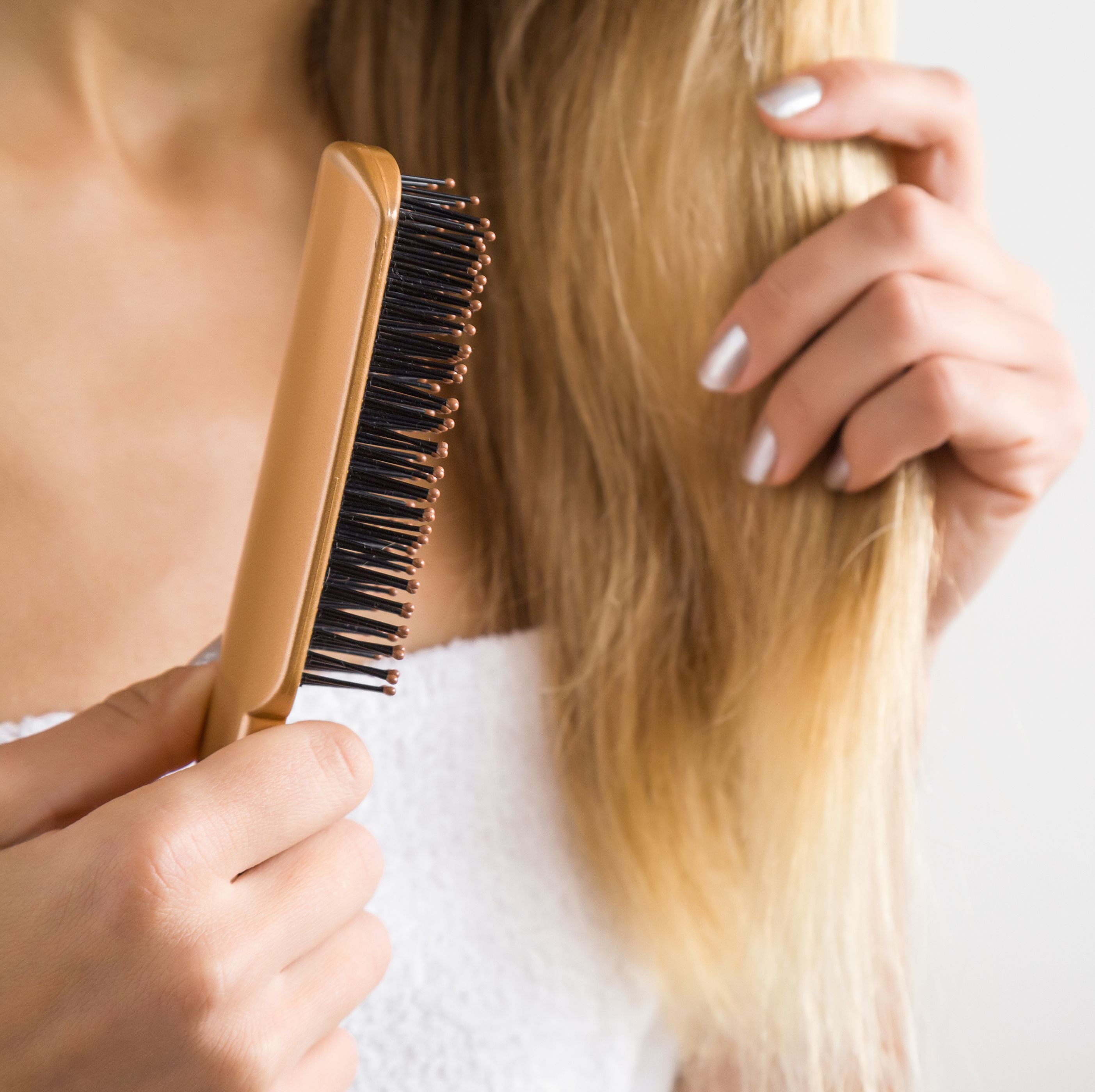 Woman's hand brushing blonde hair. Cares about a healthy and clean hair. Beauty salon. Empty place for a text on the gray background.