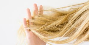 Woman's hand holding dry, blonde, tangled hair on the light gray background. Hair problem and solution. Daily women's issues.