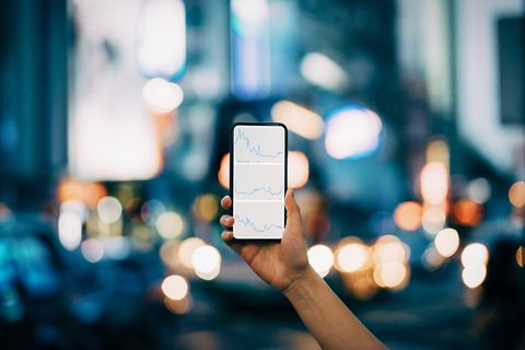 woman's hand holding smartphone showing financial trading data with stock market crash sell off against illuminated city street scene in downtown district at night