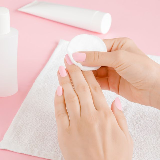 Woman's hand removing pink nail polish with white cotton pad on towel. Closeup.