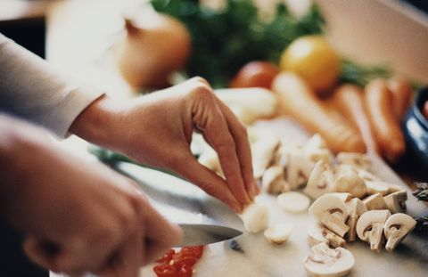 Woman's hands chopping up vegetables in kitchen, close-up